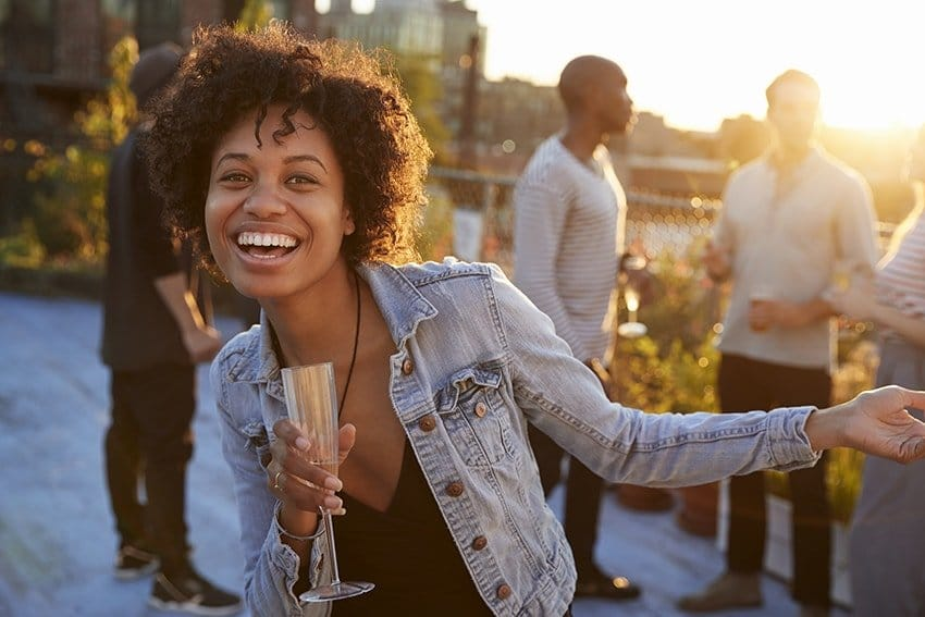 A young African American woman in New York City stands on a rooftop at a party while laughing and drinking some wine. You couldn't guess by looking at her but she has some dental implants. You care for them like natural teeth, with brushing, flossing, and regular dental visits, and they can last a lifetime like natural teeth can but are still a difference.