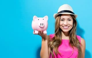 Young woman with a piggy bank on a blue background showing off her affordable cosmetic dental treatment.