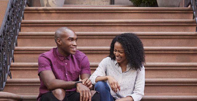 Black Midtown Manhattan couple smiling on stairway