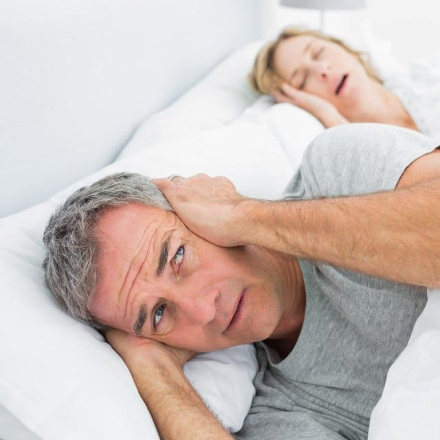 Man covering his ears while his wife snores