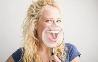 beautiful woman with magnifying glass shows off her big teeth smile