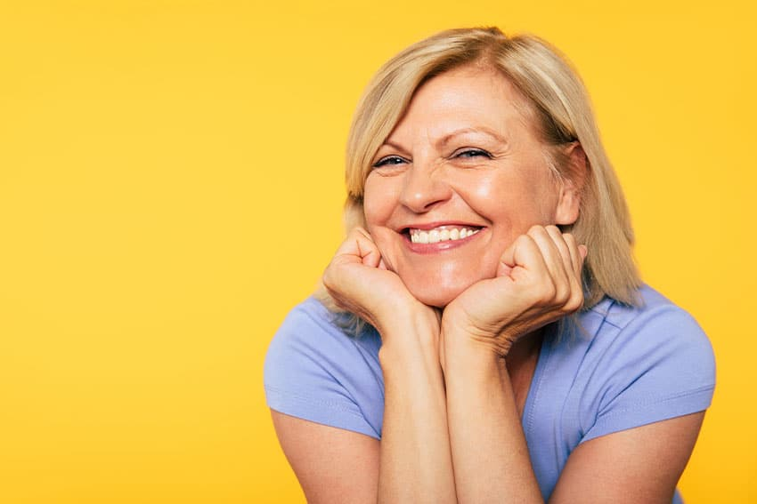 Middle-aged woman shows off her cute smile in front of a bright yellow wall