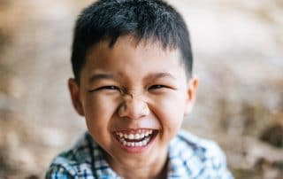 Young Asian boy showing off his big, wide smile