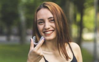attractive young woman preparing to place her Invisalign clear aligners in her mouth