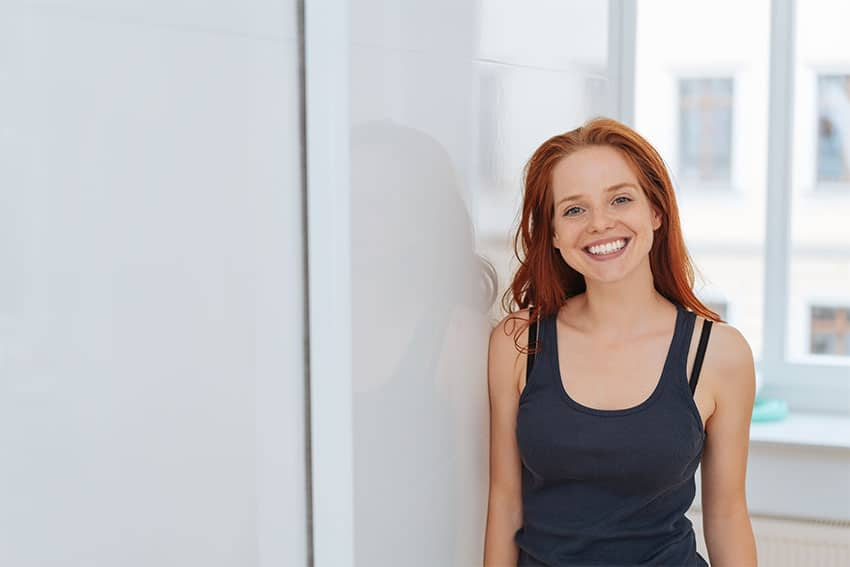 young red haired woman leans against a wall in her apartment