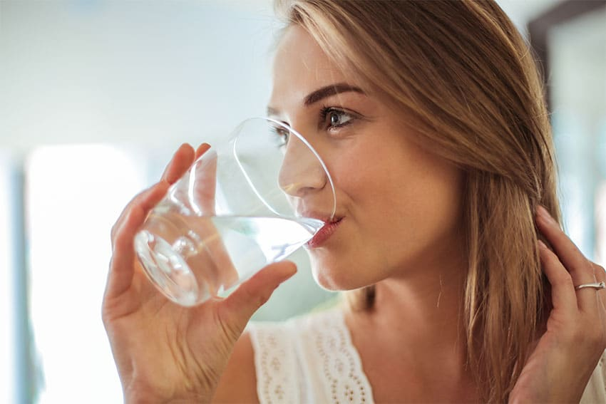 beautiful woman drinking a glass of cold water
