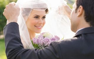 blushing bride having her veil lifted by groom