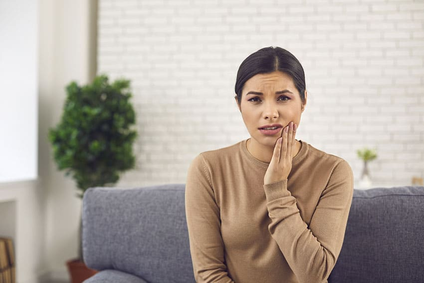 woman resting on her couch with jaw pain