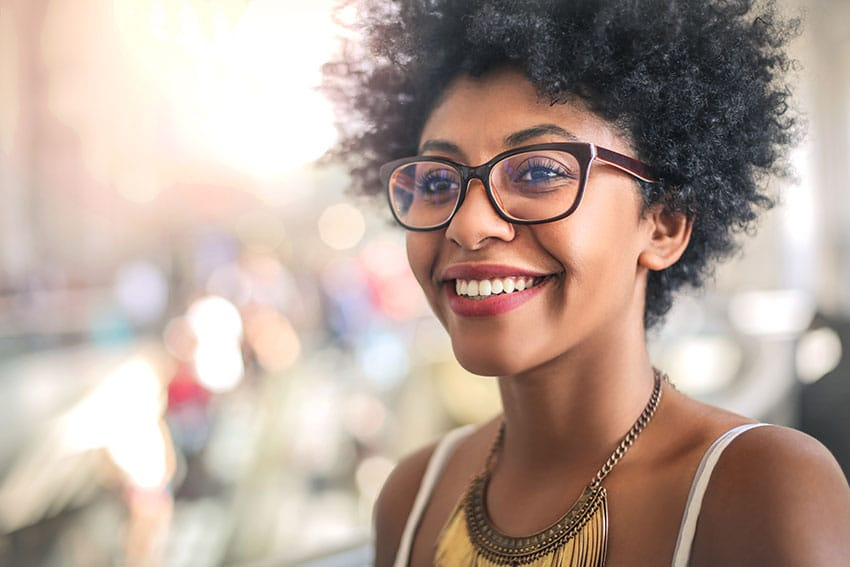 woman with curly hair and glasses shows off her white smile